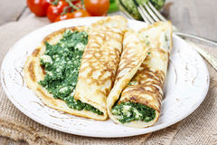 Mediterranean cuisine: crepes stuffed with cheese and spinach Stock Photos