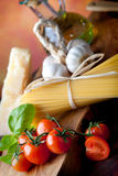 Mediterranean Cuisine: spaghetti pasta. Raw pasta with tomato, basill, garlic, Parmesan cheese and olive oil close up Royalty Free Stock Image