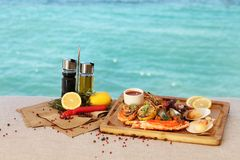 Mediterranean food is on the background of the sea. Mediterranean dish of crab, shrimp , vegetables and hot peppers on sea background royalty free stock photography