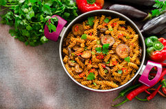 Mediterranean eggplant pasta in pot with tomatoes, red pepper and parsley on grey background. Horizontal, top view, copy space Royalty Free Stock Photography