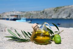 Mediterranean Feeling 2. Small bottle of olive-oil an an olive-branch with fruits on it in front of a mediterranean scene Royalty Free Stock Images