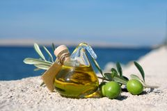 Mediterranean Feeling 3. Small bottle of olive-oil an an olive-branch with fruits on it in front of a mediterranean scene Stock Photo