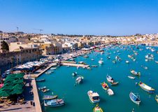 Mediterranean fishing village Marsaxlokk, Malta. Panorama with traditional eyed colorful boats Luzzu in the Harbor of Mediterranean fishing village Marsaxlokk Royalty Free Stock Photo