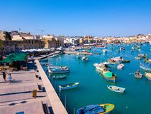 Mediterranean fishing village Marsaxlokk, Malta. Panorama with traditional eyed colorful boats Luzzu in the Harbor of Mediterranean fishing village Marsaxlokk Royalty Free Stock Images