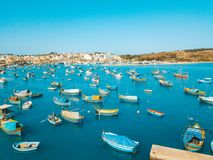Mediterranean fishing village Marsaxlokk, Malta. Panorama with traditional eyed colorful boats Luzzu in the Harbor of Mediterranean fishing village Marsaxlokk Stock Photo