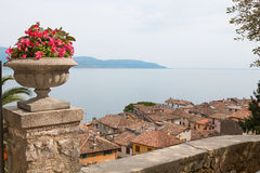 Mediterranean flowerpot on a post, view to garda lake over the r Royalty Free Stock Images