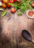 Mediterranean food background. Various fresh seasoning and tomatoes with old cooking  spoon on aged wooden background Royalty Free Stock Photos