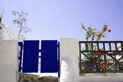 Mediterranean garden and gate. Blue wooden painted gate and white garden wall with blooming flowers and sky background, Santorini Island, Greece Royalty Free Stock Photography
