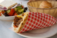Mediterranean gyros pita and greek salad. A greek gyros typically include tomato, onion, fried potatoes tzatziki in addition to the meat. Taken in Kos, Greece Stock Image