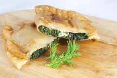 Mediterranean Hand Pie. Filled with mixed greens and feta cheese on a wooden cutting board and dill sprig Stock Photos