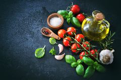 Olive oil, tomatoes, garlic, parsley, basil, spices on dark back. Mediterranean healthy cuisine. Olive oil, tomatoes, garlic, parsley, basil, spices on dark Stock Image