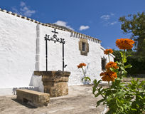 Mediterranean House. Typical Mediterranean house with a well beside the white facade. In the foreground there are orange flowers that bring color to the image Royalty Free Stock Photo