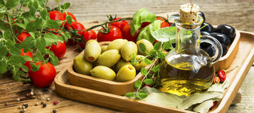 Mediterranean ingredients with olive oil and olives, spices and. Wooden tray with mediterranean ingredients, olive oil bottle, olives, tomatoes,oregano, bay Royalty Free Stock Image