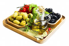 Mediterranean ingredients with olive oil and olives, spices and. Wooden tray with mediterranean ingredients, olive oil bottle, olives, tomatoes,oregano, bay Royalty Free Stock Photo