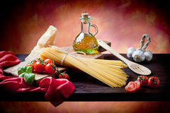Mediterranean Kitchen. Raw pasta with tomato, basill, garlic, Parmesan cheese and olive oil close up Royalty Free Stock Image