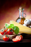 Mediterranean Kitchen. Raw pasta with tomato, basill, garlic and olive oil close up Royalty Free Stock Photography