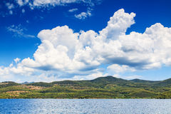 Mediterranean landscape with green island and dramatic clouds. Royalty Free Stock Photo