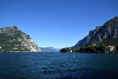 Mediterranean landscape in Italy, Lake Lecco and rocky mountains. Mediterranean landscape, Lake Lecco in Italy, blue water, blue sky, a few houses on coast and royalty free stock photography
