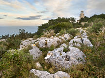 Mediterranean Lighthouse. Lighthouse located on the top of a cliff, surrounded by Mediterranean vegetation, with some rocks on the foreground Stock Image