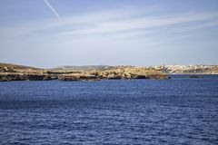Seascape with the limestone rocks of Comino Island and Mgarr Harbor in Gozo, Malta in the distance. Mediterranean Maltese seascape with limestone Comino rocks in Stock Photo