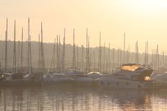 Mediterranean marina with sailing and motor yachts in the rays of the morning dawn. Sea touristic business. Infrastructure of the royalty free stock photos