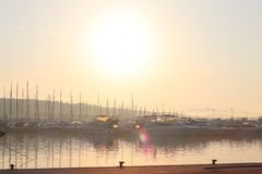 Mediterranean marina with sailing and motor yachts in the rays of the morning dawn. Sea touristic business. Infrastructure of the royalty free stock photo