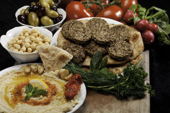 Mediterranean Meal. Mediterranean  meal with humus, olives, felafals, chickpeas, radishes and tomatoes Royalty Free Stock Photography