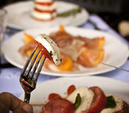 Mediterranean meal. Summer meal in the Mediterranean: Caprese salad and ham and melon Stock Photos