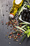 Mediterranean olives with virgin extra oil and colorful pepper over dark stone Royalty Free Stock Images