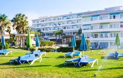 Mediterranean palm beach with empty sunbeds in morning, Paphos, Cyprus Stock Photo