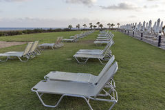Mediterranean palm beach with empty sunbeds at sunset. Stock Images