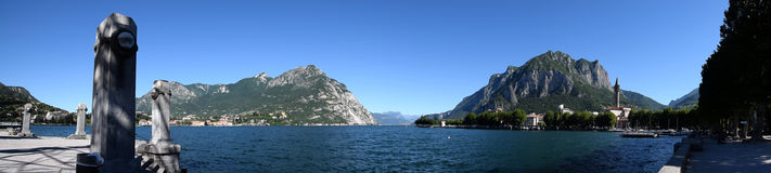 Mediterranean panorama landscape in Italy, Lake Lecco and rocky mountains. Mediterranean landscape, Lake Lecco in Italy, blue water, blue sky, a few houses on stock image