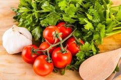 Mediterranean parsley garlic tomatoes and spaghetti. Some cherry tomatoes, parsley and garlic on a cutting board Royalty Free Stock Photos