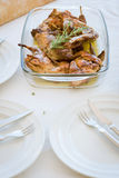 Mediterranean recipe. Traditional roasted rabbit with rosemary. Baking dish with roasted rabbit and spices (rosemary and thyme). Traditional Mediterranean stock photos