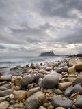 Mediterranean Rocky Beach. Seascape on a rocky beach with a mountain on the foreground Stock Photo