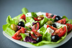 Mediterranean salad with feta and olives. Low angle view of a plate of fresh healthy Mediterranean salad with feta, tomato and olives on a bed of leafy greens Stock Image