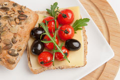 Mediterranean sandwich. With herbs, olives, basil, tomatoes and cheese on a plate Royalty Free Stock Photos
