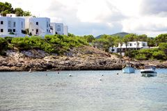 Mediterranean scene of the coast of Portinatx in Ibiza. View from the water to the mountains and little white houses in a cloudy day. Soft bright light over the Royalty Free Stock Photography