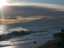 Mediterranean sea with mount Etna. In the background at sunset in winter royalty free stock images
