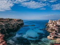 Landscape view of Popeye village bayh in Malta. Mediterranean sea view from the coastline of Popeye village. Crystal clear blue water, yellow stone rocky shores Stock Photo