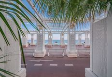 Mediterranean Sea and white colonnade on Promenade des Anglais at sunset in Nice France. Mediterranean Sea, white colonnade, benches and palm trees on Promenade stock photos