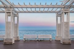 Mediterranean Sea and white colonnade on Promenade des Anglais at sunset in Nice France. Mediterranean Sea and white colonnade and benches on Promenade des stock photography