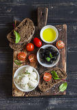 Mediterranean snack - mozzarella, olives, rye ciabatta bread, cherry tomatoes on a rustic cutting board Stock Images