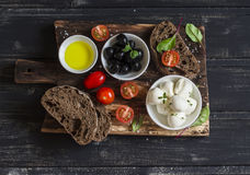 Mediterranean snack - mozzarella, olives, rye ciabatta bread, cherry tomatoes on a rustic wooden cutting board Stock Photos