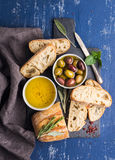 Mediterranean snacks set. Olives, oil, herbs and sliced ciabatta bread on black slate stone board over painted dark blue Stock Photo