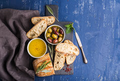 Mediterranean snacks set. Olives, oil, herbs and sliced ciabatta bread on black slate stone board over painted dark blue. Background, top view, copy space royalty free stock photos