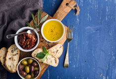 Mediterranean snacks set. Olives, oil, herbs and sliced ciabatta bread on yellow rustic oak board over painted dark blue Stock Images