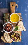 Mediterranean snacks set. Olives, oil, herbs and sliced ciabatta bread on yellow rustic oak board over painted dark blue Royalty Free Stock Photography