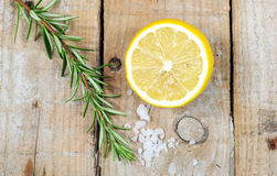 Mediterranean spices - rosemary, lemon, sea salt. On wooden background Royalty Free Stock Photos