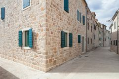 Mediterranean stone built houses. Empty street enclosed by old, stone built, attached houses with colorful windows in small and beautiful Šepurine village on Stock Photography